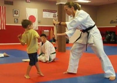kid working with instructor to learn how to punch