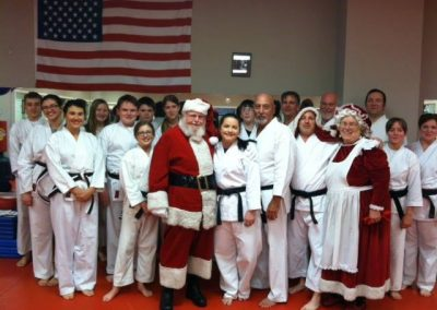 karate class in uniform posing with santa claus